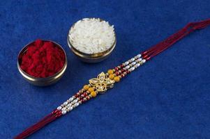 braccialetto rakhi, chicchi di riso e kumkum su sfondo blu