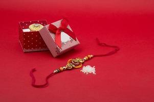 eleganti gioielli rakhi su sfondo rosso.