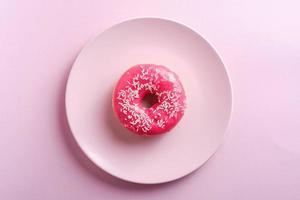 Ciambella rosa brillante con granelli bianchi sul piatto rosa