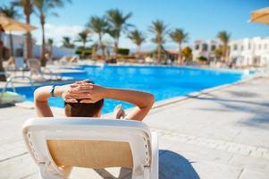 donna posa su un lettino a bordo piscina foto