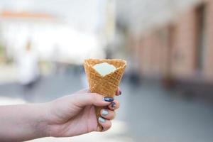 la mano della ragazza tiene il gelato alla vaniglia foto