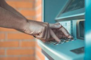 il cliente bancario inserisce il codice della carta di credito nella macchina bancomat foto