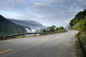 strada accanto alla foresta nebbiosa e montagne con cielo nuvoloso foto