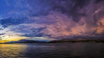 nuvole sopra montagne e acqua foto