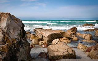 spiaggia con rocce sotto il cielo blu