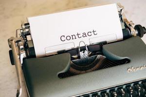 macchina da scrivere verde con la parola contatto digitata foto