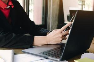 primo piano della donna di affari che lavora in smartphone della tenuta dell'ufficio