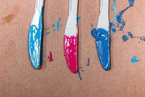 colori acrilici applicati su tre coltelli di plastica foto