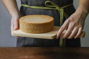 tagliere della holding della persona con il pan di Spagna foto