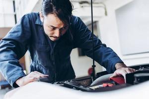 meccanico di auto che lavora in garage foto