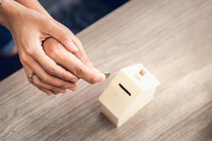 mani di coppie che depositano una moneta in banca foto