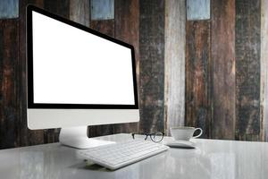 computer con schermo bianco sul tavolo con sfondo sfocato