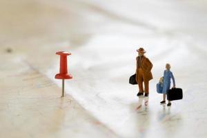 piccole figurine umane in legno stanno su una mappa foto