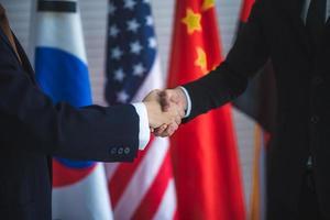 uomini d'affari si stringono la mano, sfondo bandiera internazionale