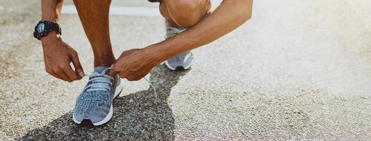 uomo che lega le scarpe da corsa si prepara per la corsa. stile di vita sano e sport. banner con spazio di copia.