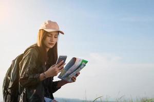 donna navigando con mappa e telefono in mano foto