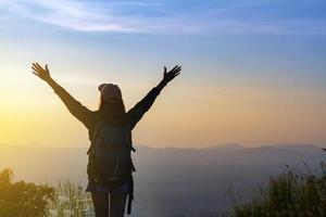 la donna ha alzato le braccia sul picco di montagna foto
