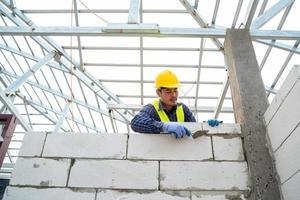 muratore che costruisce muro di mattoni