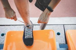 persona che lega i lacci delle scarpe