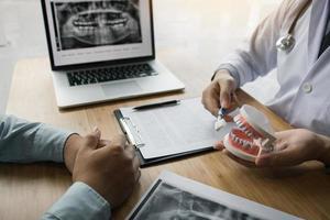 dentista che mostra al cliente come pulire i denti foto