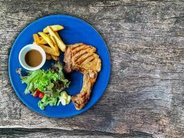 bistecca con l'osso sul piatto e sullo sfondo di legno