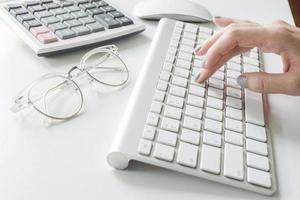 primo piano della donna che scrive sulla tastiera foto