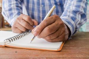 primo piano di uomo che scrive nel quaderno