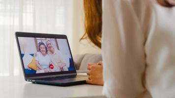 giovane femmina asiatica che per mezzo della videochiamata del computer portatile con la famiglia.