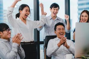 un gruppo di giovani imprenditori festeggia in ufficio foto