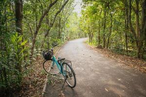 una bicicletta parcheggiata su una strada deserta nella foresta tailandese