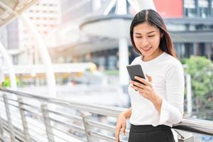 Ritratto di donna asiatica che tiene smartphone foto