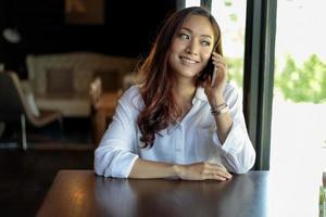 giovane donna asiatica alla caffetteria sul telefono foto
