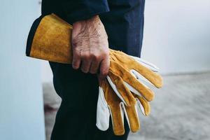 primo piano dell'uomo che tiene i guanti da lavoro gialli foto