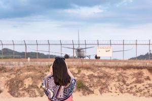 donna che fotografa aeroplano foto