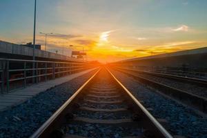 binari ferroviari e luce solare arancione foto
