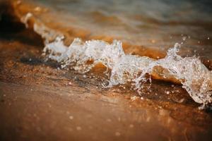 primo piano delle onde sulla spiaggia foto