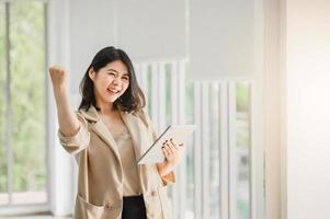 donna asiatica che tiene compressa digitale e che alza il suo braccio su foto