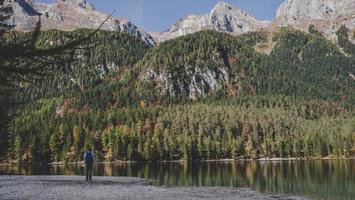 persona in piedi davanti all'acqua e alle montagne