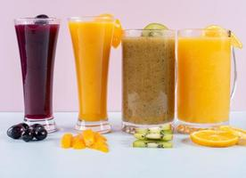 bicchieri di succo e frutta sul tavolo di legno foto