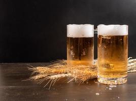 due bicchieri di birra con steli di grano foto