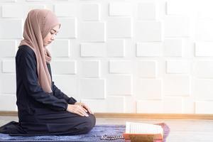 donne musulmane vestite di hijab nero, pregando foto