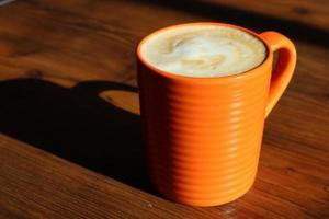 primo piano di una tazza di caffè arancione foto