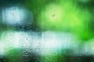 goccioline d'acqua che scorre dal vetro trasparente dopo la pioggia foto