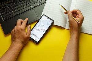 mani con laptop, cellulare, taccuino e penna