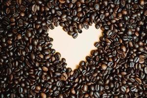 a forma di cuore incorniciato da chicchi di caffè tostati