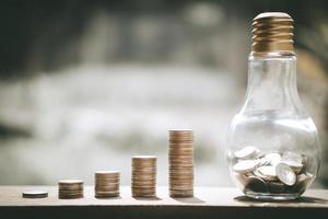 pile di monete accanto alla lampadina foto