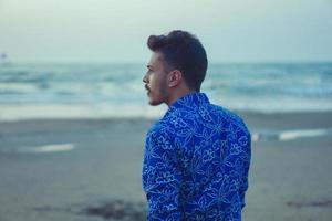 giovane che cammina sulla spiaggia foto