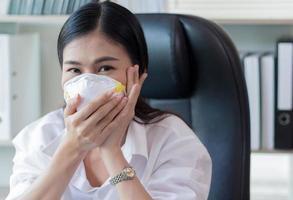 donna seduta in ufficio che indossa la maschera