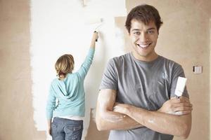 uomo fiducioso con la donna utilizzando il rullo di vernice