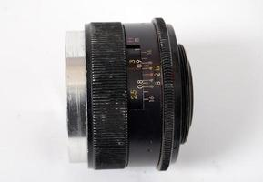 un vecchio obiettivo della fotocamera a controllo manuale isolato su bianco foto